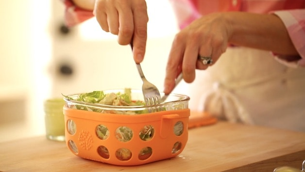 A person cutting salad in an orange container