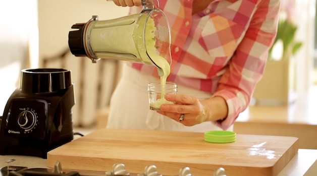 pouring an avocado lime dressing into a small container