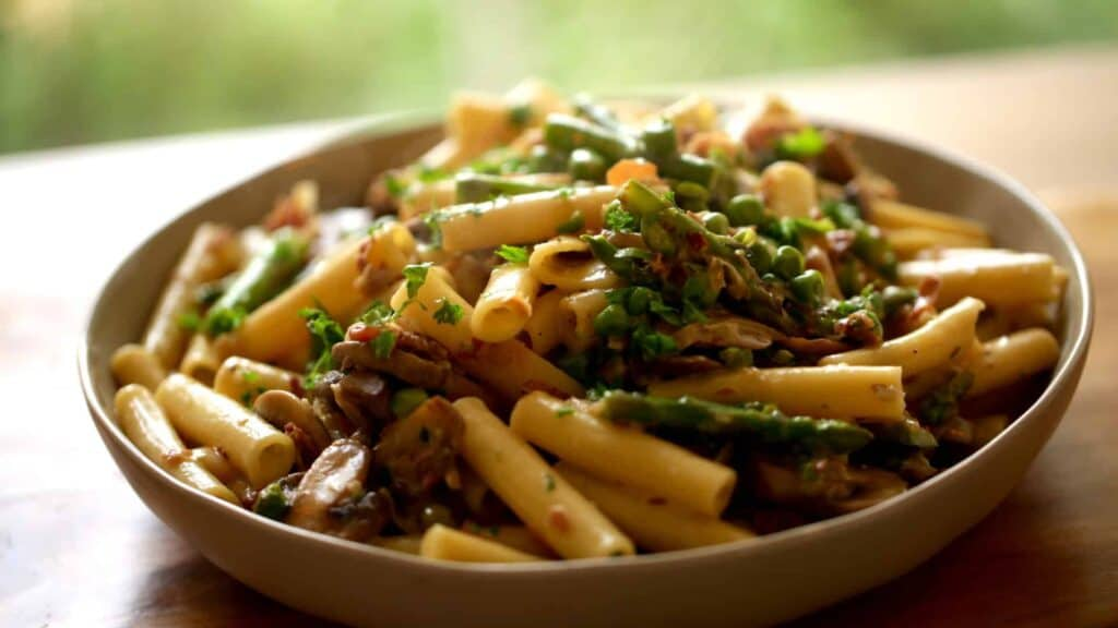 Large platter of pasta with fresh parsley, peas asparagus and proscuitto
