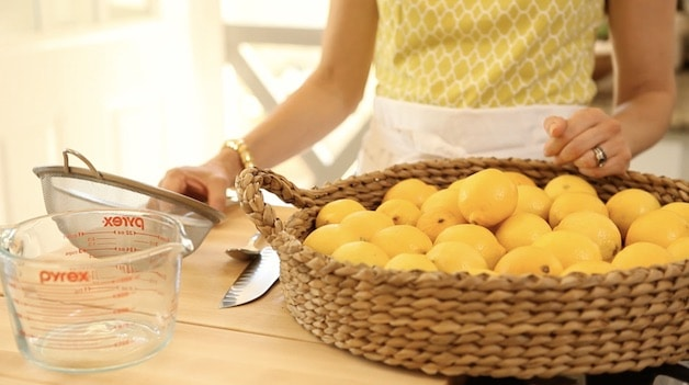 Fresh lemons in a basket with a sieve and a pyrex pitcher