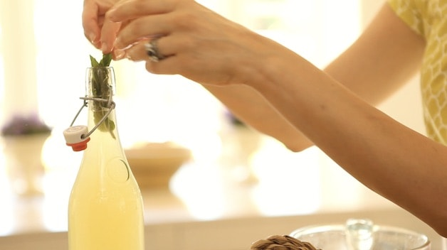 adding sprig of mint to a bottle of lemonade