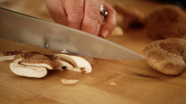 slicing shitake mushrooms on a cutting board