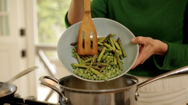 adding frozen peas and fresh asparagus to a pot of boiling water with pasta