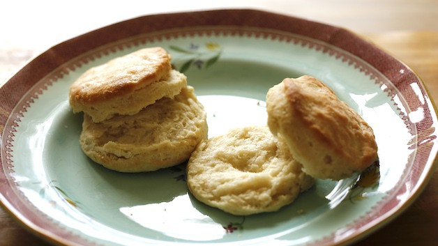 two buttermilk biscuits split open on blue plate