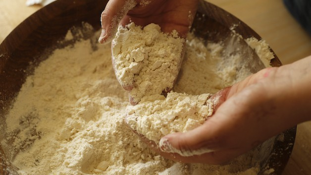 Hands in a wooden bowl of flour and butter mixture creating a coarse meal