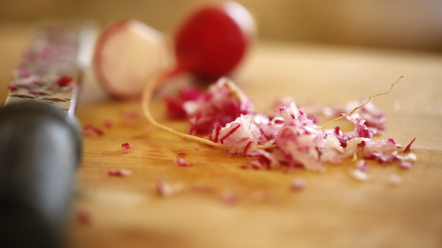 radishes on cutting board grated with zester in background