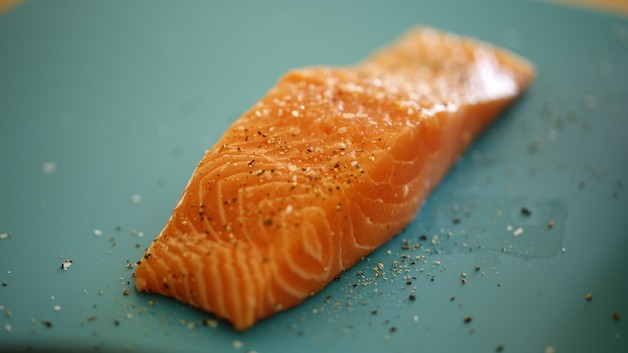 Salmon filet with salt and pepper on blue mat