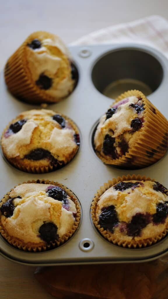 Blueberries muffins in a Jumbo Muffin Tin with one Muffin Turned Over