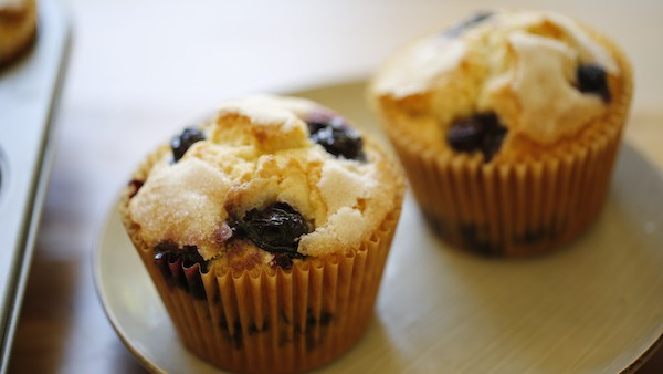 Two Blueberry Muffins on a gray plate