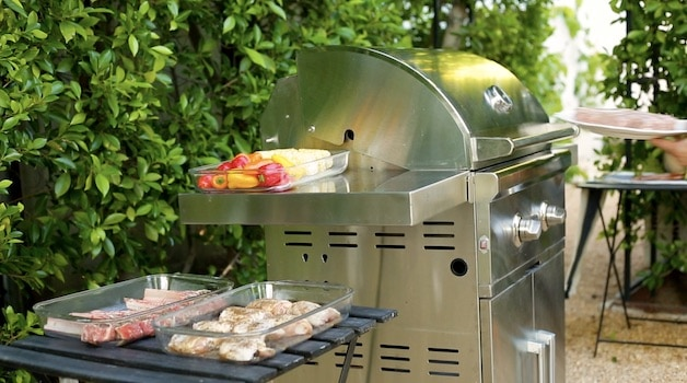 a gas grill with platters of food ready for grilling