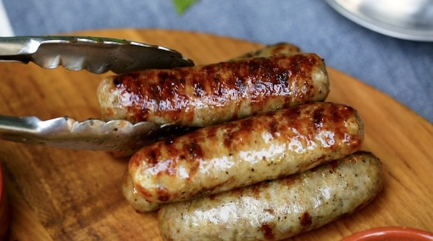 a tong placing grilled sausages on a serving board