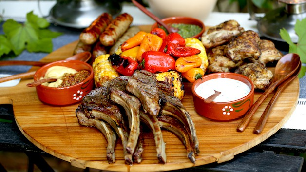 A mixed grill dinner of meat and vegetables on a board