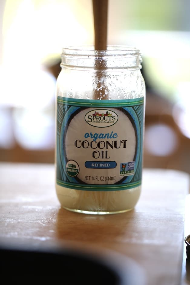 a jar of coconut oil on a cutting board