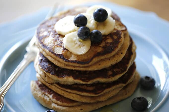 4 Ota Flour Pancakes on a Blue Plate topped with Honey and fruit