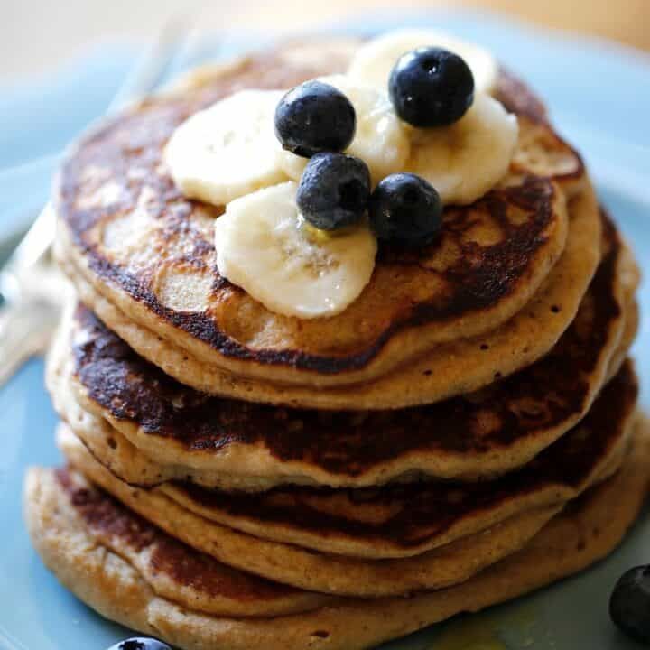 a stack of Oat flour pancakes with blueberries and bananas on a blue plate