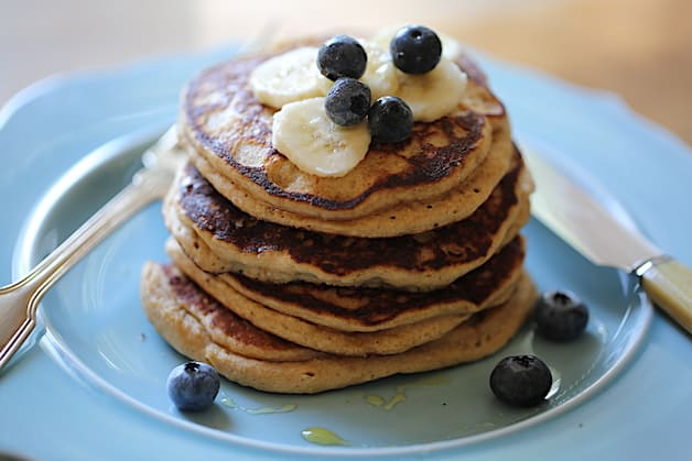 a stack of Oat Flour Pancakes topped with Blueberries and bananas on a blue plate