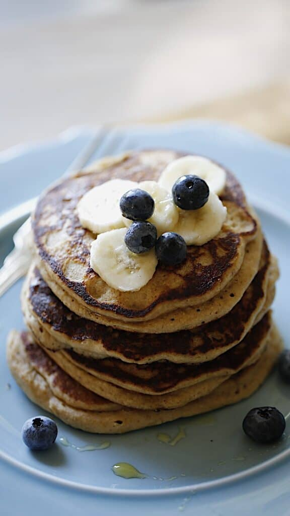 a vertical image of a blue plate piled high with Oat Floiur Pancakes with Bananas and Blueberries on top