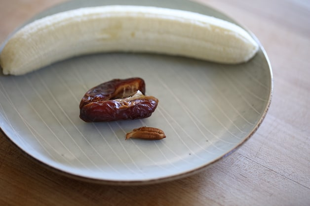 a peeled banana and a split open date with pit on a plate