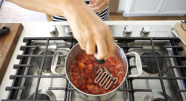 mashing strawberries in a pot with a potato masher