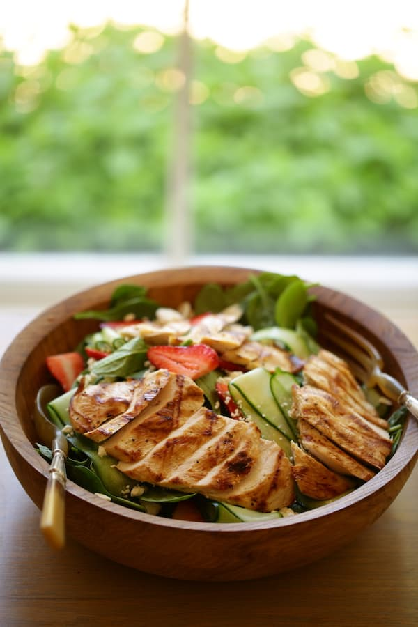 Vertical Image of Strawberry Spinach Salad with Grilled Chicken and Poppy Seed Dressing