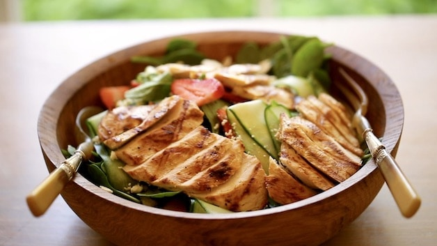 Grilled chicken on a bed of spinach salad with strawberries
