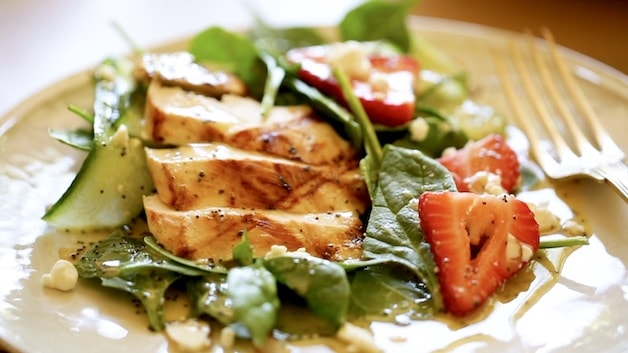 a plate a spinach salad with grilled chicken strawberries and goat cheese