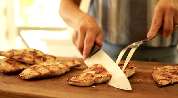 slicing grilled chicken on the diagonal with a chef knife