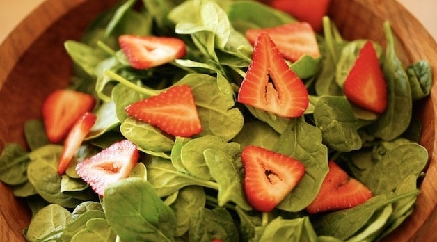sliced strawberries on a spinach salad