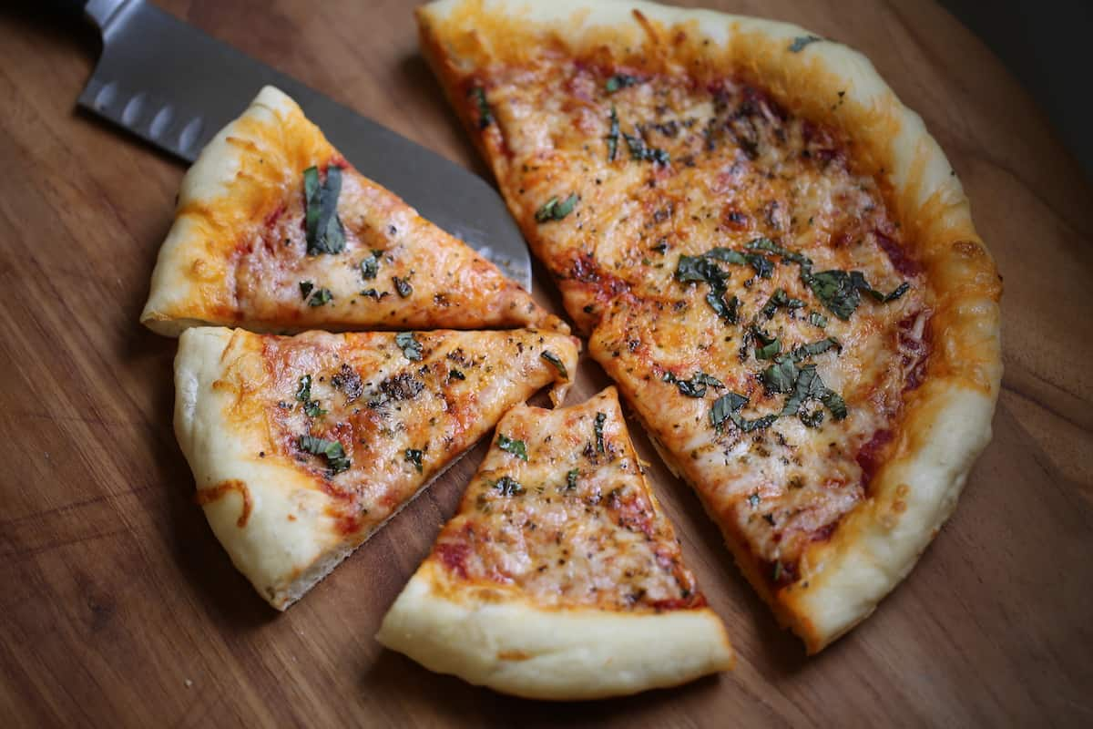 A slice of pizza sitting on top of a wooden cutting board, with Cheese