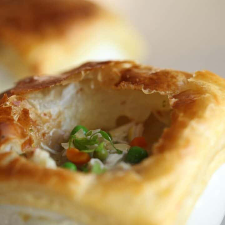 Chicken pot pie with puff pastry torn open to see interior