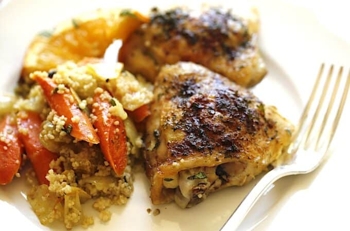 A close up of a plate of food with a fork, with Chicken and Couscous