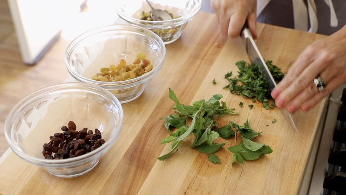 chopping fresh mint on a cutting board with bowls of dried fruit to the side