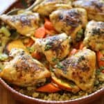 a vertical image of roasted chicken thighs on a bed of couscous