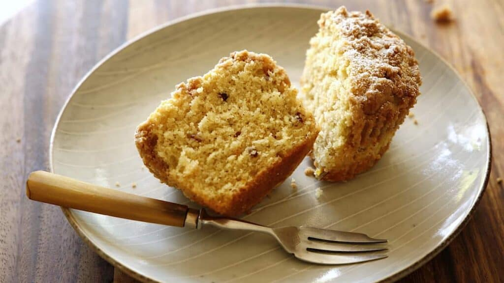 a crumb cake muffin cut in half on a plate with a fork