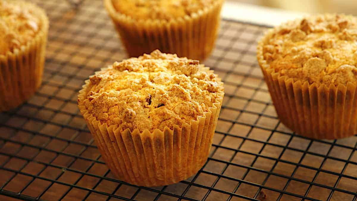 Crumb cake muffins on a cooling rack before powdered sugar