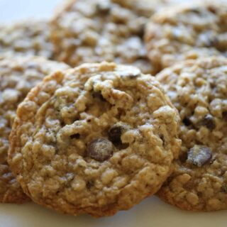 a close up shot of a Oatmeal Chocolate Chip Cookie on a marble cakestand