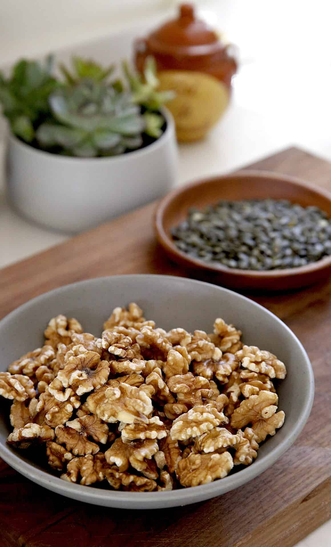 Walnuts and Pepitas in bowls on a cutting board