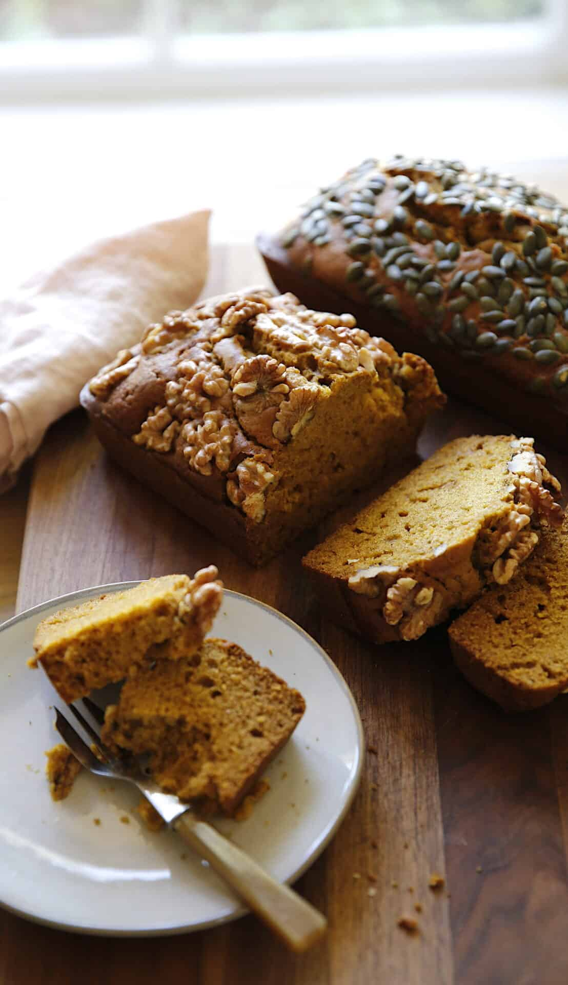 2 loaves of pumpkin bread sliced and a slice placed on a plate with a fork