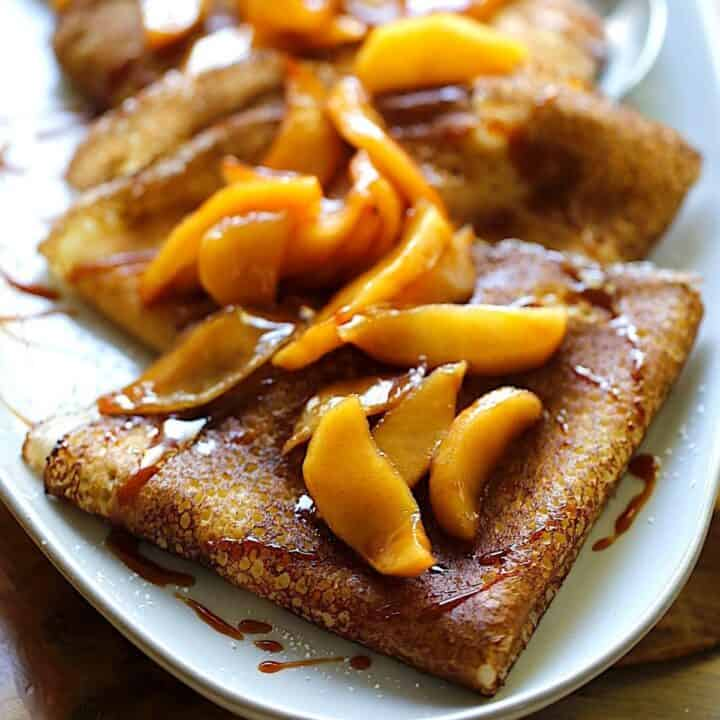 A platter of apple cinnamon crepes folded into triangles topped with caramel sauce