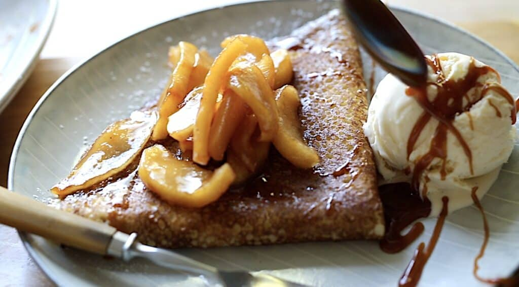 An apple crepe on a plate with a scoop of ice cream being drizzled with caramel sauce