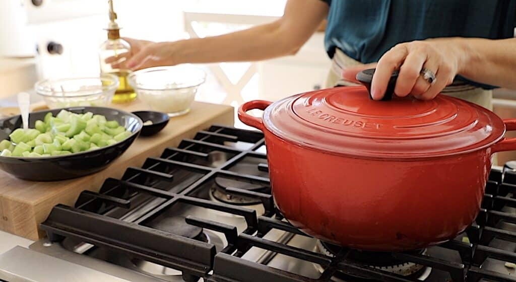 a red Dutch oven ready to cook vegetables for soup
