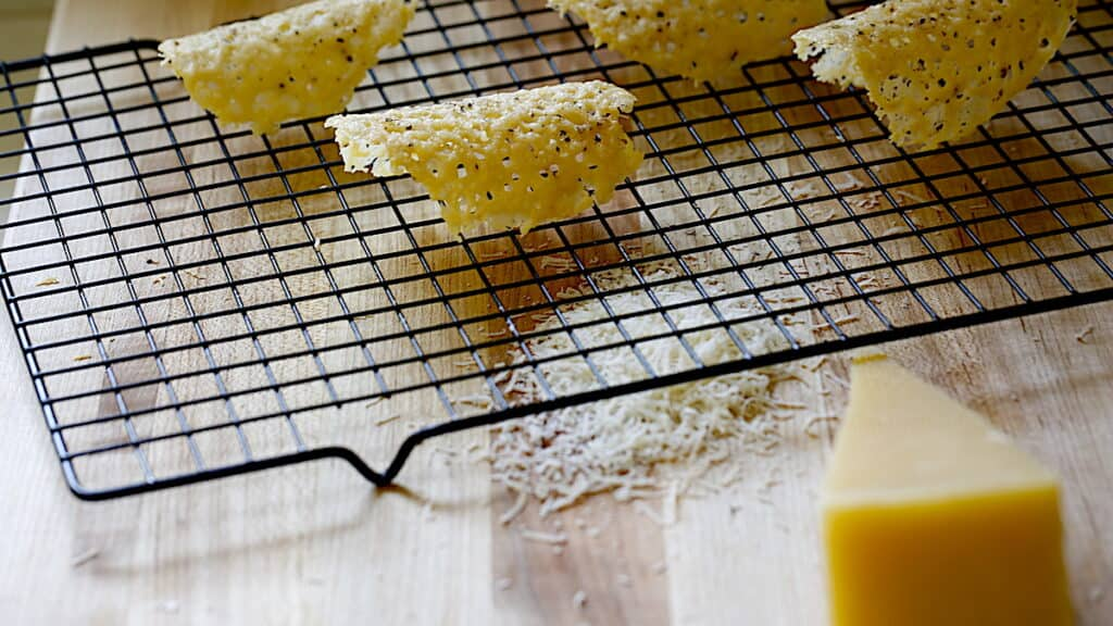 Several Parmesan Tuiles cooling on a cooling rack