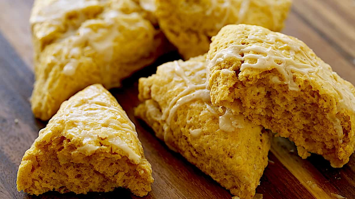 a few pumpkin scones on a board with one cut in half to see interior fluffy texture