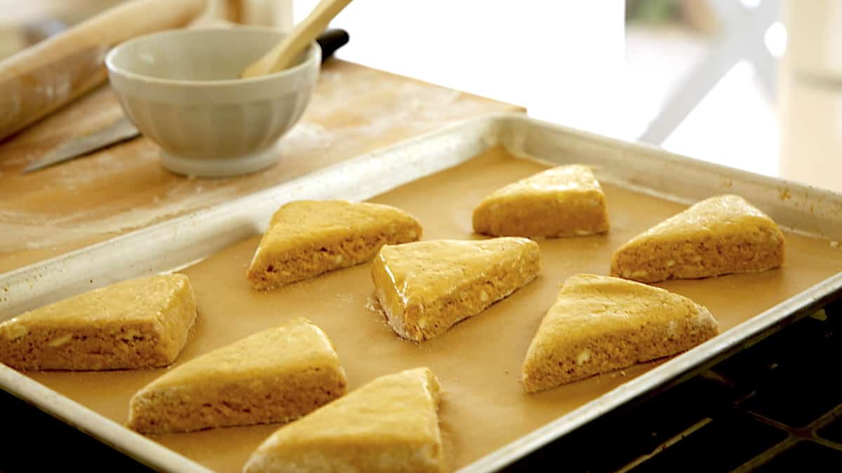 scone triangles on a baking sheet ready for the egg wash