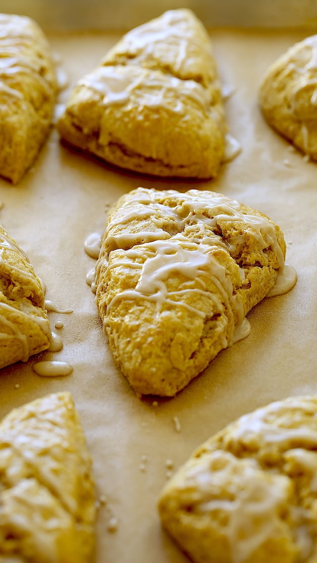 Vertical image of pumpkin scones on a baking sheet with chai glaze