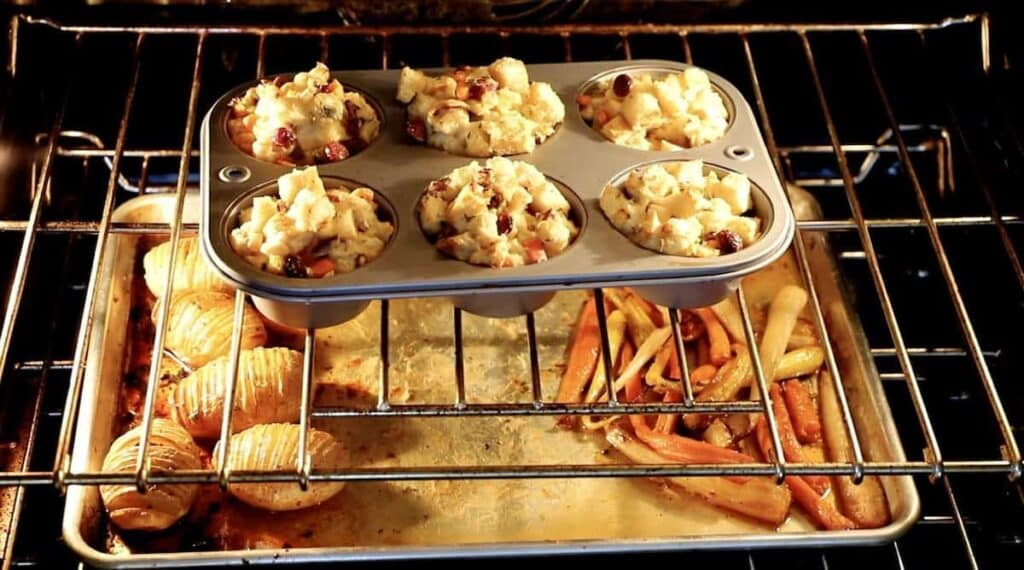 interior of an oven with stuffing muffins on top rack and a sheet pan of carrots and potatoes on the lower rack