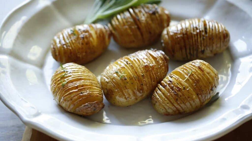 Perfectly Roasted Hasselback Potatoes on a white platter with a garnish of fresh sage