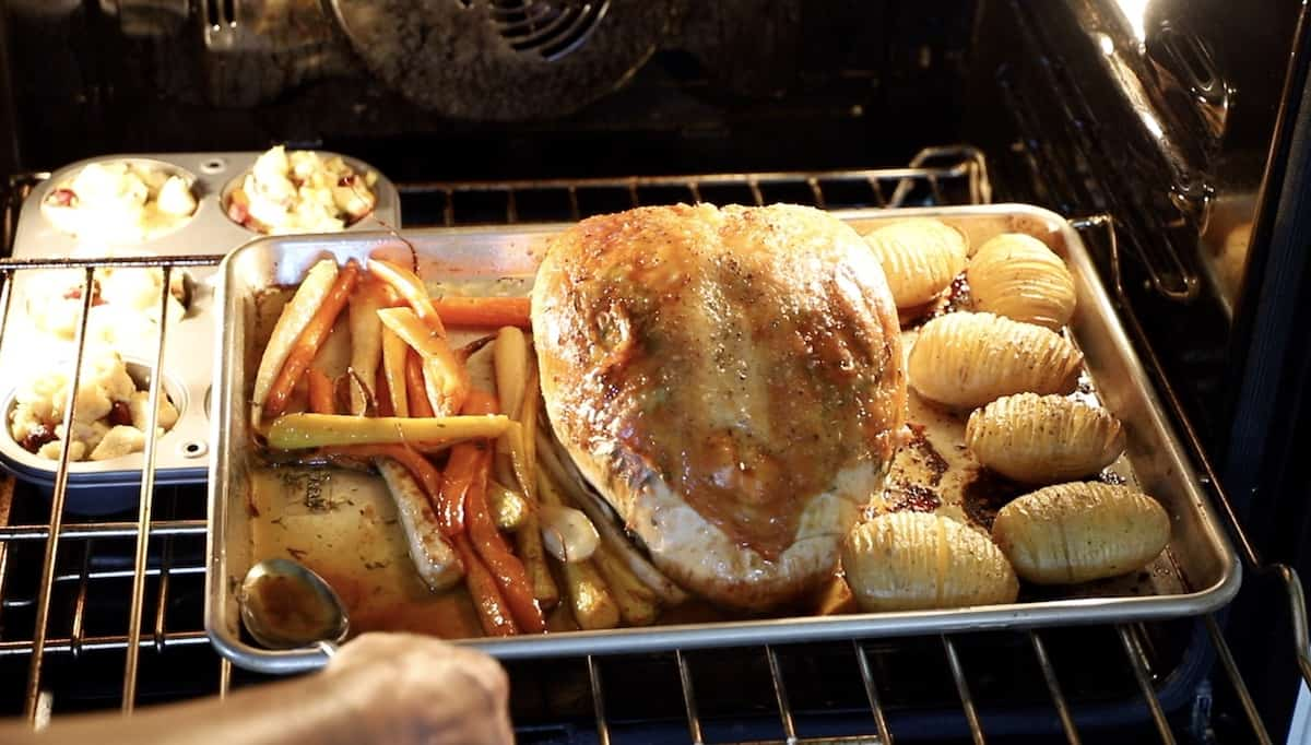 a person spooning the pan gravy from a sheet pan of a Turkey and vegetables roasting in the oven