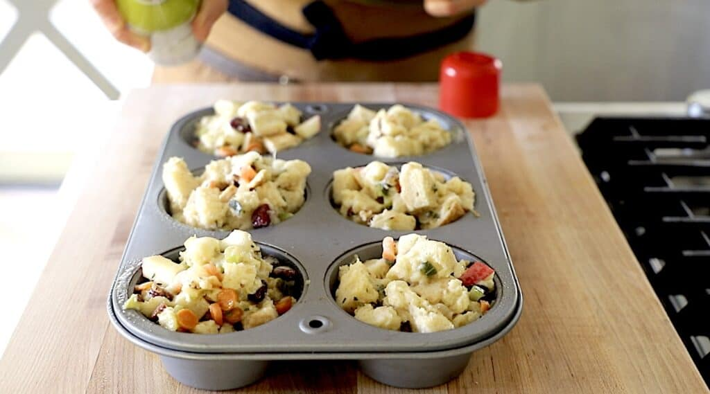 a Jumbo Muffin tin with stuffing muffins filled and a can of olive oil spray spraying the tops of them