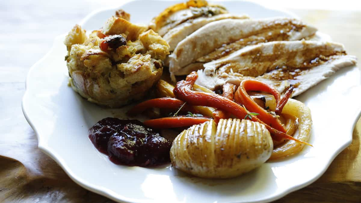a white plate with turkey and graving and Thanksgiving sides on it